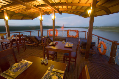 [picture] The upper deck of the Bassac II at night, ready for dinner while cruising the Mekong near Caibe