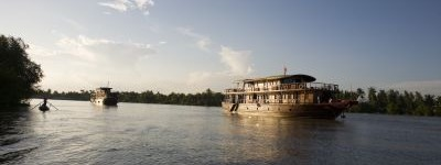 [picture] Two Bassac boats at sunset on one of the Mekong's tributaries