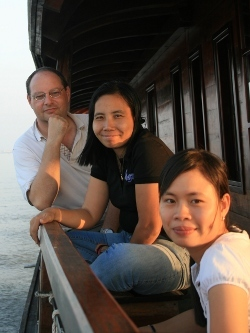 [picture] Thanh, our French-speaking cruise director, and the shipowners on board a Bassac on a Mekong cruise